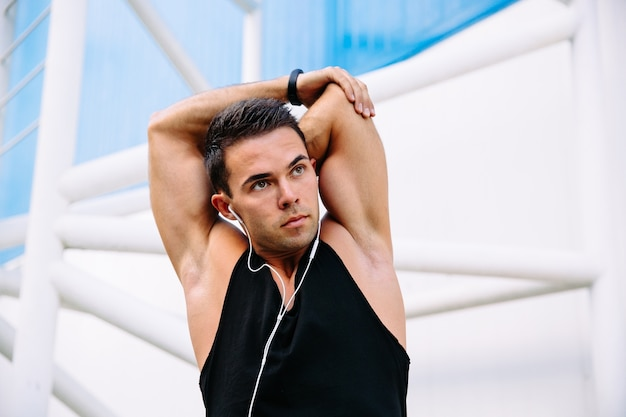 Attractive young sportsman in earphones doing exercises for arms while stretching