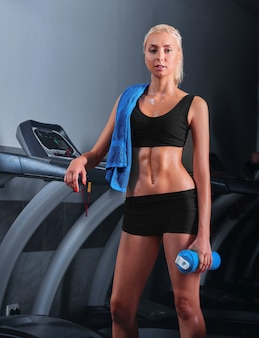 Attractive young sportswoman resting after running on treadmill