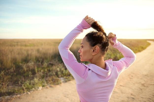 Привлекательная юная спортсменка связывает волосы в хвост перед пробежкой по пустынной сельской степной дороге. концепции спорта, тренировок и тренировок на открытом воздухе