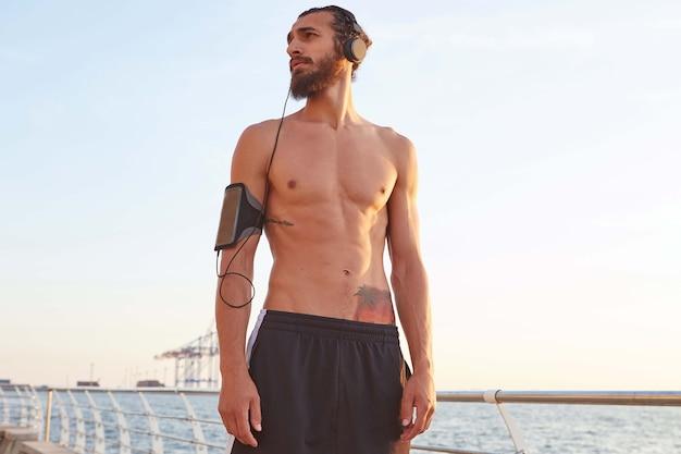 매력적인 젊은 스포티 한 수염 난 남자는 해변에서 익스트림 스포츠 후 휴식을 취하고 멀리보고 헤드폰으로 노래를 듣고,