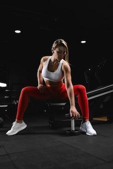 Привлекательная молодая спортивная женщина сидит на скамейке и поднимает гантель в тренажерном зале