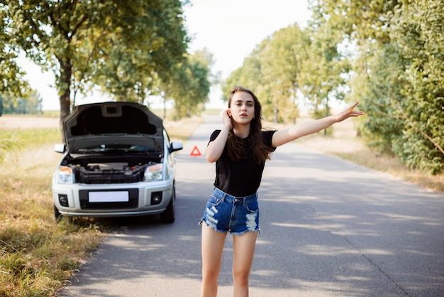 Attractive young student woman tries to stop passerby car and ask for a help because her car has broken