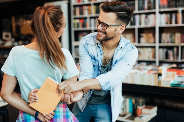 Attractive young students man and woman choosing books in the bookstore.