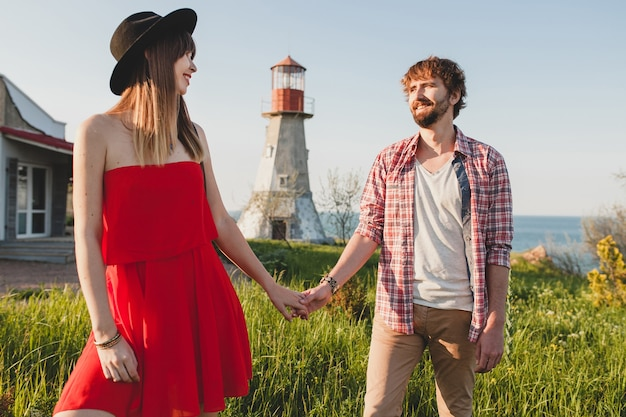Attractive young stylish couple in love in countryside, indie hipster bohemian style, weekend vacation, summer outfit, red dress, green grass, holding hands