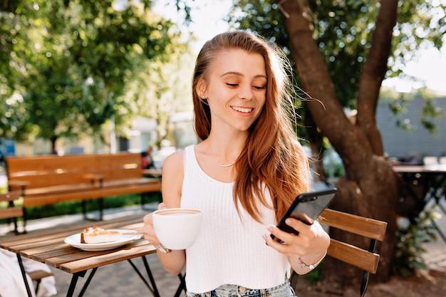 スマートフォンで座っている魅力的な若いスタイリッシュな流行に敏感な女性