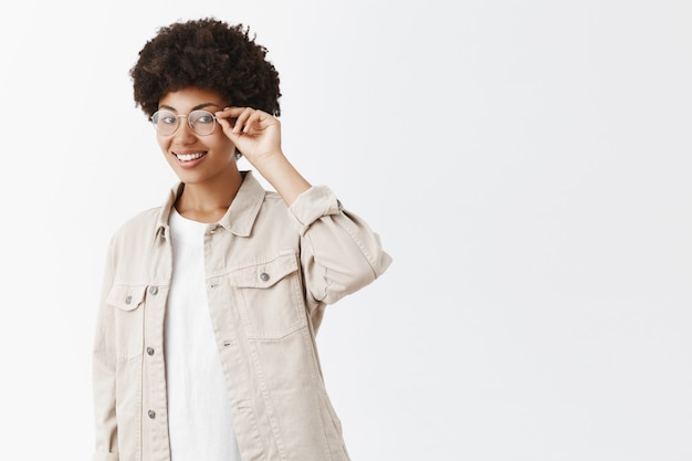 Attractive young and stylish modern african american with afro hairstyle in glasses and beige shirt, standing half-turned over gray wall, touching rim and gazing with cute smile