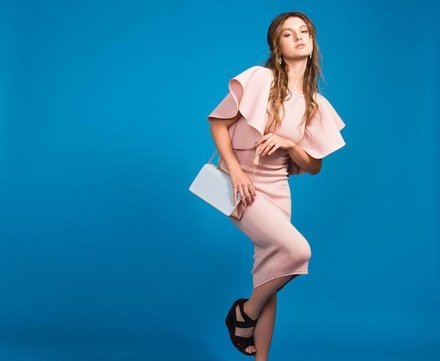 유행 핸드백을 들고 핑크 럭셔리 드레스, 여름 패션 트렌드, 세련된 스타일, 블루 스튜디오 배경에 매력적인 젊은 세련된 섹시한 여자