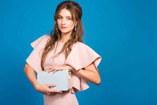 ピンクの豪華なドレス、夏のファッションのトレンド、シックなスタイル、ブルースタジオの背景、トレンディなハンドバッグを保持している魅力的な若いスタイリッシュなセクシーな女性