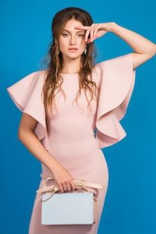 Attraente giovane donna sexy alla moda in abito di lusso rosa, tendenza moda estiva, stile chic, sfondo blu studio, tenendo la borsa alla moda