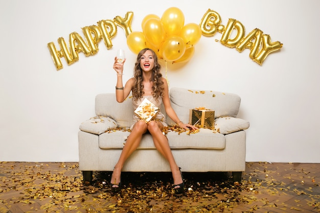 Attractive young stylish woman celebrating birthday, sitting on sofa with presents, golden confetti and airballons, party mood, smiling happy, wearing party dress, drinking champagne