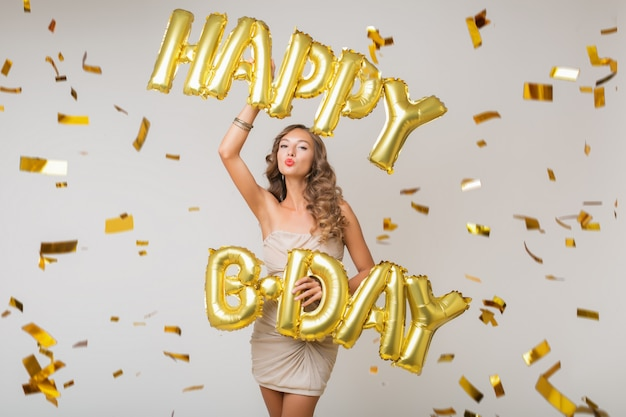 Attractive young stylish woman celebrating, holding air balloons happy birthday letters, golden confetti flying, smiling happy, isolated, wearing party dress