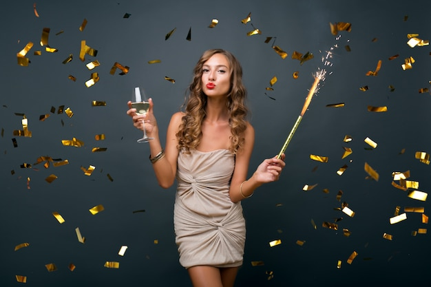 Attractive young stylish woman celebrating new year, drinking champagne, golden confetti flying, smiling happy, isolated, wearing party dress