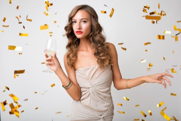 Привлекательная молодая стильная женщина празднует новый год, пьет шампанское, летит золотое конфетти, улыбается счастливым, в вечернем платье