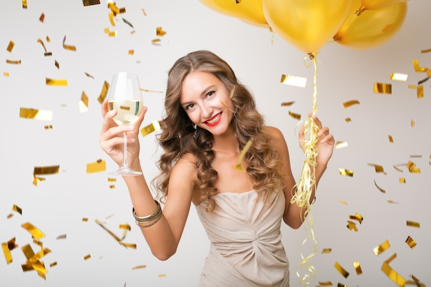 Attractive young stylish woman celebrating new year, drinking champagne holding air balloons, golden confetti flying, smiling happy, isolated, wearing party dress