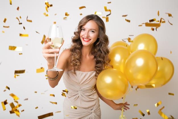 새 해를 축하하는 매력적인 젊은 세련된 여자, 공기 풍선을 들고 샴페인을 마시고, 황금색 색종이 비행, 행복 미소, 흰색, 절연, 파티 드레스를 입고