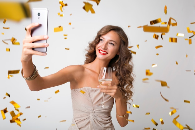 Attractive young stylish woman celebrating new year, drinking champagne making selfie photo on phone, golden confetti flying, smiling happy, isolated, wearing party dress