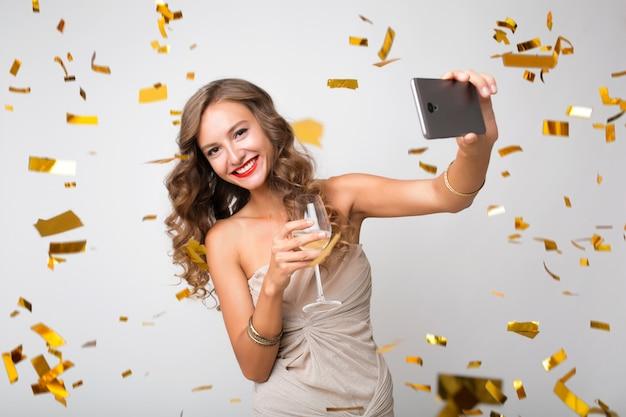 Attraente giovane donna elegante che celebra il nuovo anno, bevendo champagne facendo selfie foto sul telefono, coriandoli dorati volanti, sorridendo felice, isolato, indossando abiti da festa