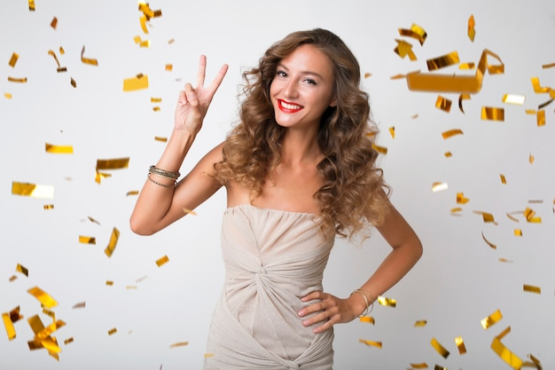 Attractive young stylish woman celebrating new year, golden confetti flying, smiling happy, isolated, wearing party dress, makeup and hairstyle