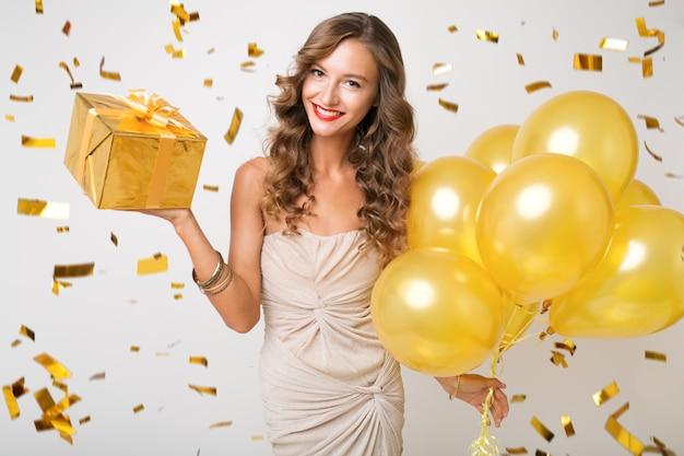 Привлекательная молодая стильная женщина празднует новый год, держит воздушные шары и преподносит сюрприз, летит золотое конфетти, улыбается счастливым, изолированным, в вечернем платье