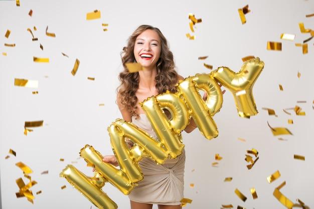 Привлекательная молодая стильная женщина празднует новый год, держа воздушные шары счастливыми буквами, золотое конфетти, летящее, улыбаясь счастливым, изолированным, в праздничном платье