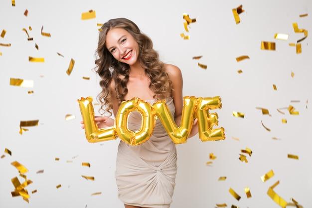 Привлекательная молодая стильная женщина празднует новый год, держа в руках любовные письма воздушных шаров, летающее золотое конфетти, улыбаясь счастливым, изолированным, в вечернем платье