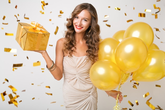 Attractive young stylish woman celebrating new year, holding air balloons and presents surprise, golden confetti flying, smiling happy, isolated, wearing party dress