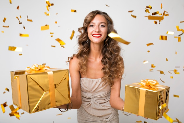 Attractive young stylish woman celebrating new year, holding presents in box, golden confetti flying, smiling happy, wearing party dress, luxury makeup and hairstyle