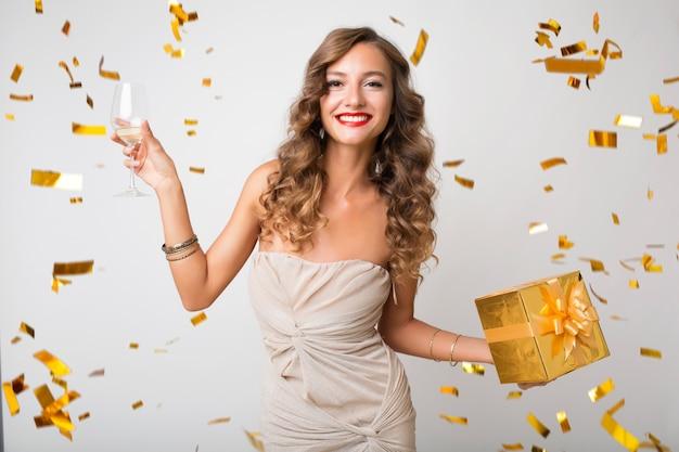 Attraente giovane donna elegante che celebra il nuovo anno, che tiene i regali in scatola, coriandoli dorati che volano, sorridendo felice, indossando l'abito da festa