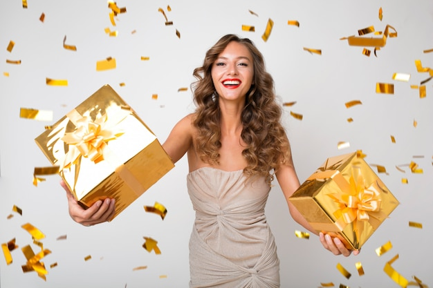 Attractive young stylish woman celebrating new year, holding presents in box, golden confetti flying, smiling happy, wearing party dress