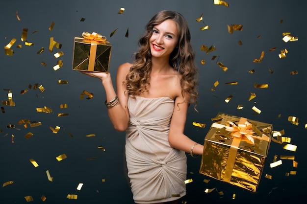 Привлекательная молодая стильная женщина празднует новый год, держит подарки в коробке, летит золотое конфетти, улыбается счастливой, носит праздничное платье, роскошный макияж и прическу