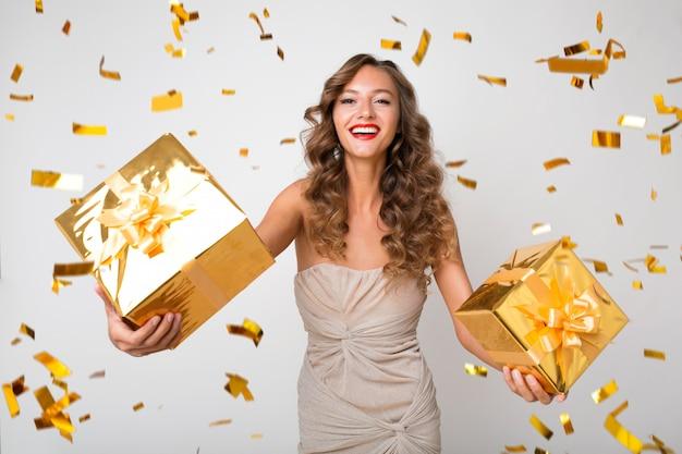 Привлекательная молодая стильная женщина празднует новый год, держит подарки в коробке, летит золотое конфетти, улыбается счастливой, в вечернем платье