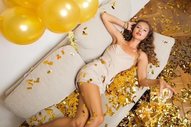 Привлекательная молодая стильная женщина празднует новый год, сидя на диване с подарками, золотыми конфетти и воздушными шарами, праздничным настроением, счастливой улыбкой, в праздничном платье, пьет шампанское