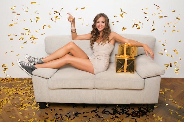 Привлекательная молодая стильная женщина празднует новый год, сидя на диване с подарками, золотым конфетти, праздничным настроением, счастливой улыбкой, в вечернем платье, пьет шампанское