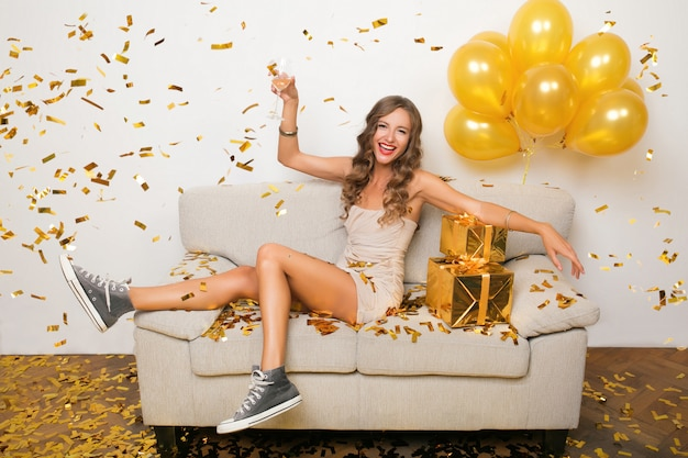 Attractive young stylish woman celebrating new year, sitting on sofa with presents, golden confetti and airballons, party mood, smiling happy, wearing party dress, drinking champagne