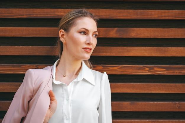 Привлекательная молодая стильная женщина, стоящая у деревянной стены