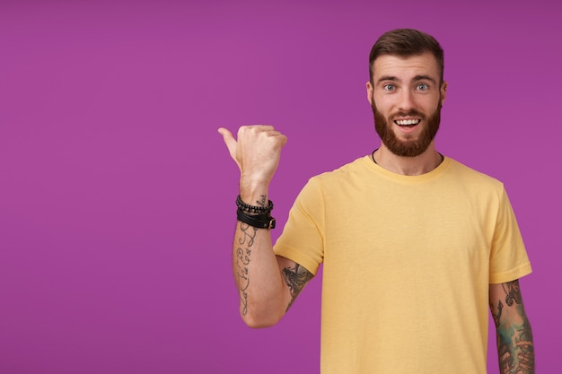 トレンディなヘアカットを喜んでそして広く笑って、紫色の上に立っている間、上げられた親指で脇に見せて、魅力的な若い入れ墨されたブルネット