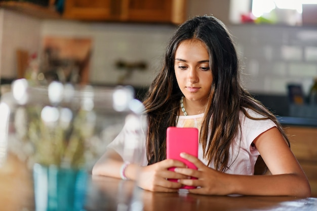 매력적인 10대 소녀가 실내에서 테이블에 앉아 쉬면서 휴대전화로 미디어를 읽거나 보고 있다