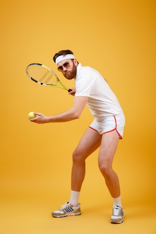 Привлекательный молодой теннисист в очках