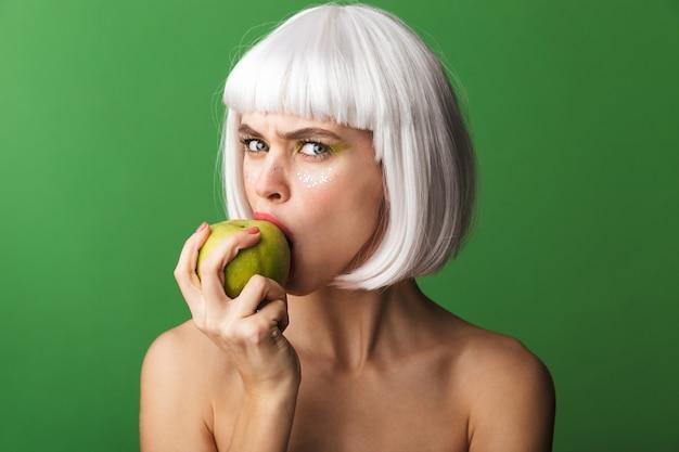 リンゴを噛んで孤立して立っている短い白い髪を身に着けている魅力的な若いトップレスの女性