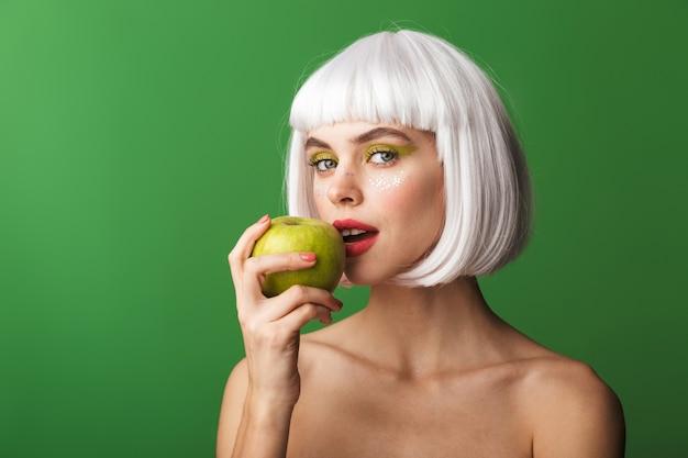 孤立して立っている短い白い髪を着て、リンゴを食べる魅力的な若いトップレスの女性
