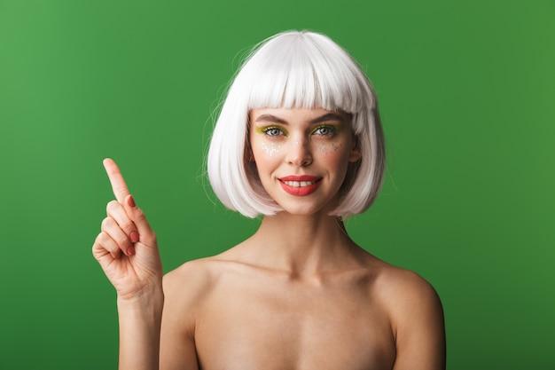 Привлекательная молодая женщина топлес, одетая в короткие белые волосы, стоя изолированно, указывая пальцем на копию пространства