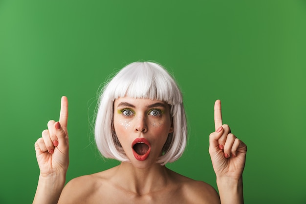 Attractive young topless woman wearing short white hair standing isolated, pointing finger up at copy space