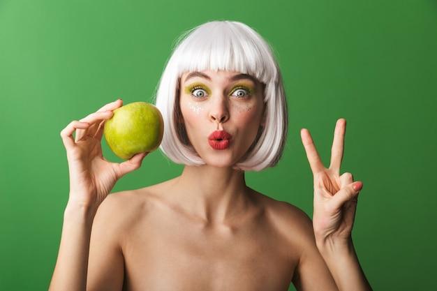 リンゴを見せて、孤立して立っている短い白い髪を身に着けている魅力的な若いトップレスの女性