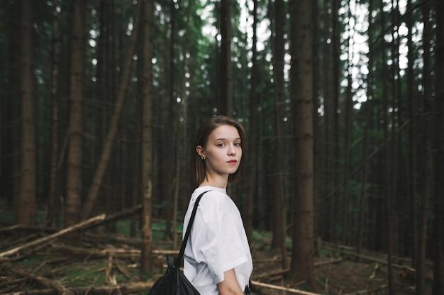 山のモミの森を歩いてカメラを見ている魅力的な若い観光客の女性