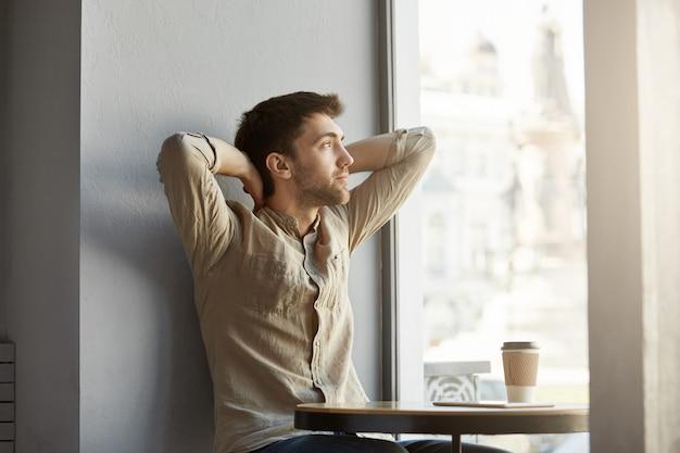 魅力的な若い無精ひげを生やした男がカフェに座って、コーヒーを飲み、彼の頭の後ろに手でウィンドウを見て、ビジネス会議後に疲れ