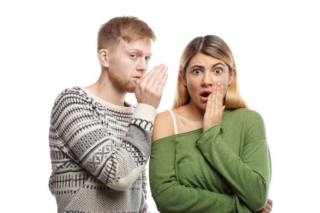 Attraente giovane maschio con la barba lunga che condivide segreti o sussurra pettegolezzi nell'orecchio della sua ragazza stupita, che sta fissando con la bocca spalancata, scioccata da informazioni inaspettate