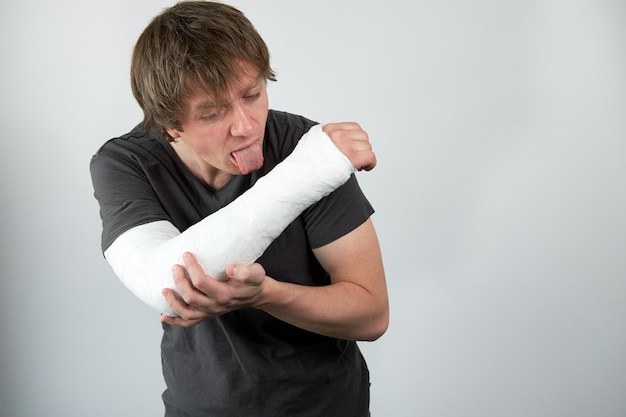 Attractive young upset caucasian man trying to lick hisr plaster.