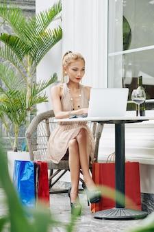 Привлекательная молодая вьетнамская женщина сидит за столом в летнем кафе и работает на ноутбуке