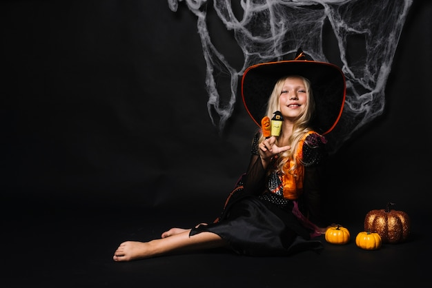 Attractive young witch with toys and pumpkins