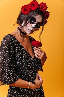 매력적인 젊은여자가 다 정하게, 아름 다운 붉은 장미와 함께 포즈. 카니발에 대 한 얼굴 예술을 가진 여자의 사진입니다.